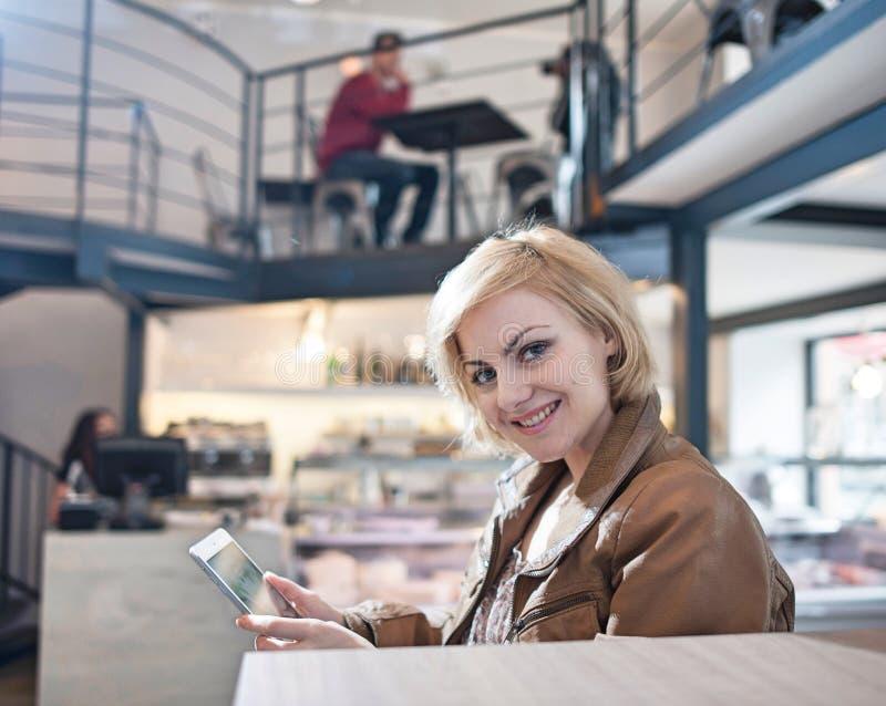 Retrato de la mujer joven sonriente que usa la tableta en café fotos de archivo libres de regalías