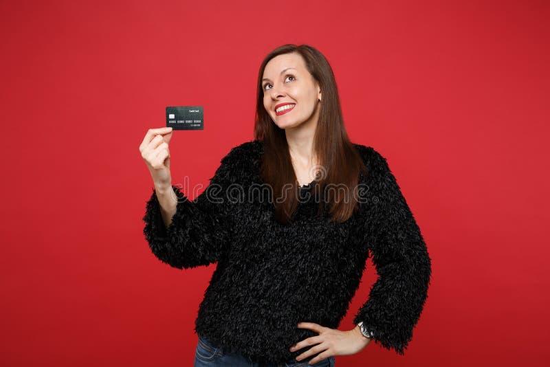 Retrato de la mujer joven thinkful en el suéter negro de la piel que mira para arriba, sosteniendo la tarjeta de banco de crédito fotografía de archivo
