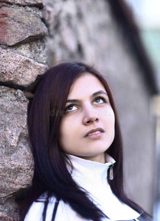 Retrato de la mujer joven triste en fondo de la pared de piedra fotografía de archivo