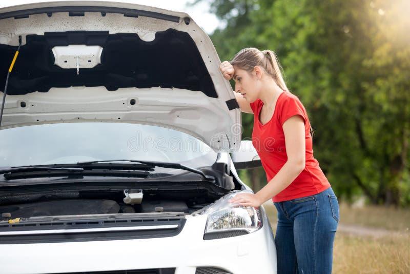Retrato de la mujer joven triste que se inclina en la capilla abierta del coche y que mira el motor quebrado fotografía de archivo
