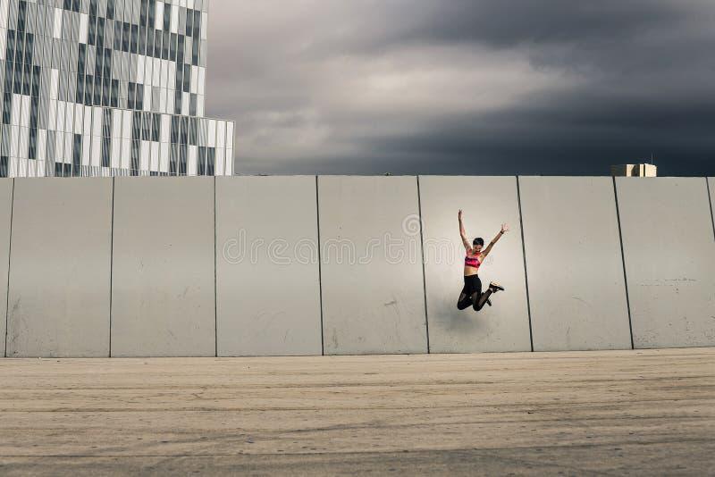 Retrato de la mujer joven y atractiva que salta al lado de la pared en parque urbano imágenes de archivo libres de regalías