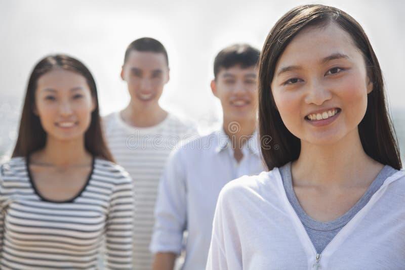 Retrato de la mujer joven y de amigos en la playa fotos de archivo