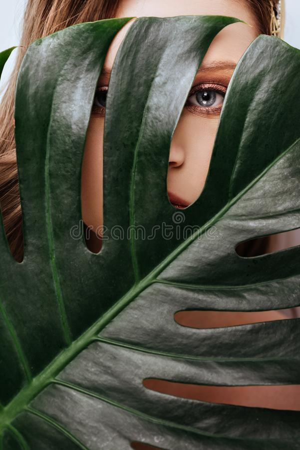 Retrato de la mujer joven y hermosa en hojas tropicales imagen de archivo libre de regalías