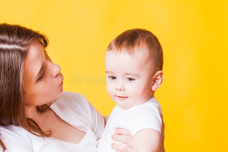 Retrato de la mujer joven y de un pequeño bebé imagen de archivo