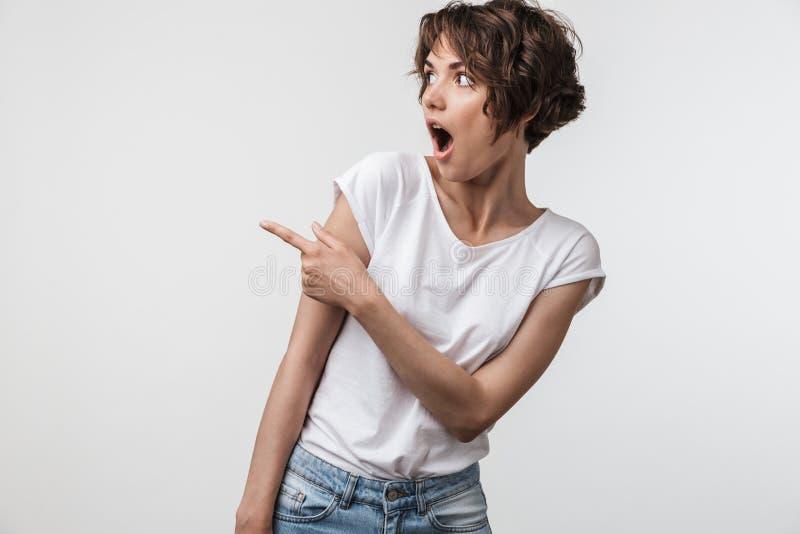 Retrato de la mujer linda con el pelo corto en el júbilo básico de la camiseta y el finger el señalar en el copyspace fotos de archivo libres de regalías