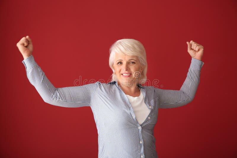 Retrato de la mujer madura acertada feliz en fondo del color imagenes de archivo