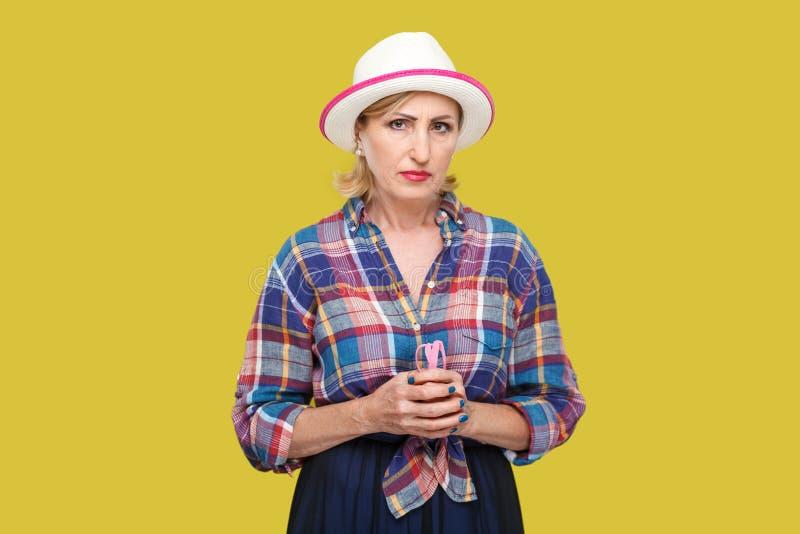 Retrato de la mujer madura elegante moderna triste o seria en estilo sport con la situación blanca del sombrero y de mirar la cám imagenes de archivo