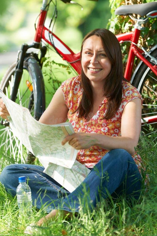 Retrato de la mujer madura en paseo del ciclo en el campo mA de lectura imagen de archivo
