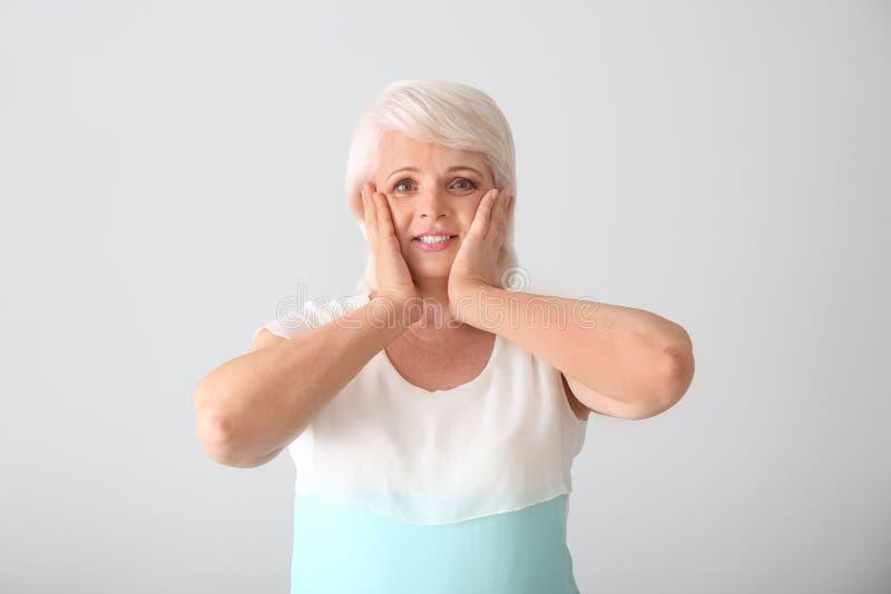 Retrato de la mujer madura feliz en fondo ligero fotografía de archivo