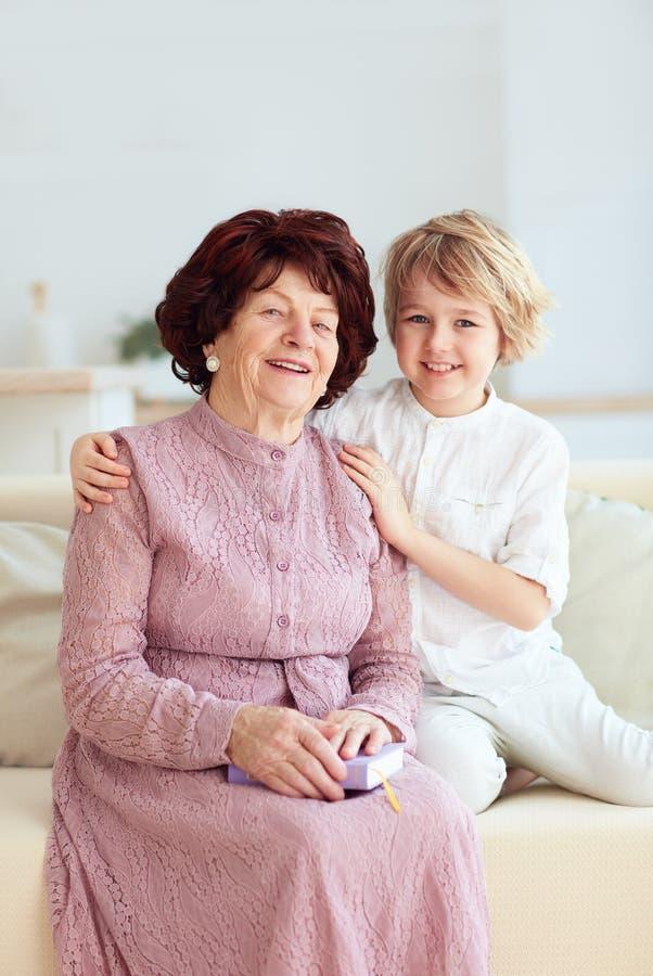 Retrato de la mujer madura hermosa 80 años con su grande-nieto en casa imagen de archivo libre de regalías