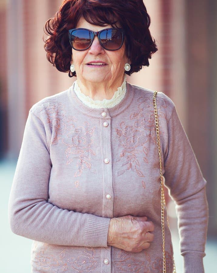 Retrato de la mujer madura hermosa, de moda 80 años que caminan en la calle de la ciudad fotos de archivo libres de regalías