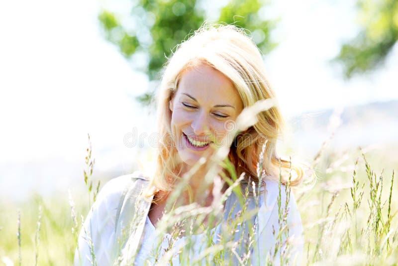 Retrato de la mujer madura hermosa que se coloca en prado foto de archivo libre de regalías
