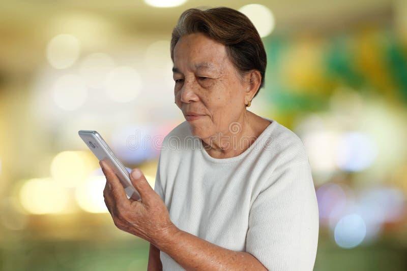 Retrato de la mujer mayor asiática que sonríe con usar el teléfono móvil y el fondo colorido del bokeh imagenes de archivo