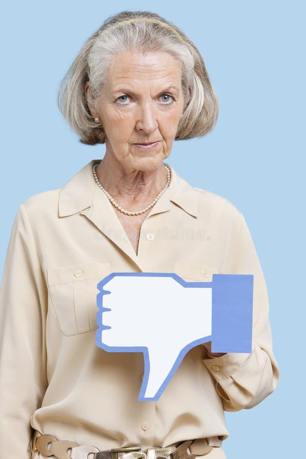 Retrato de la mujer mayor con el botón falso de la aversión contra fondo azul foto de archivo libre de regalías