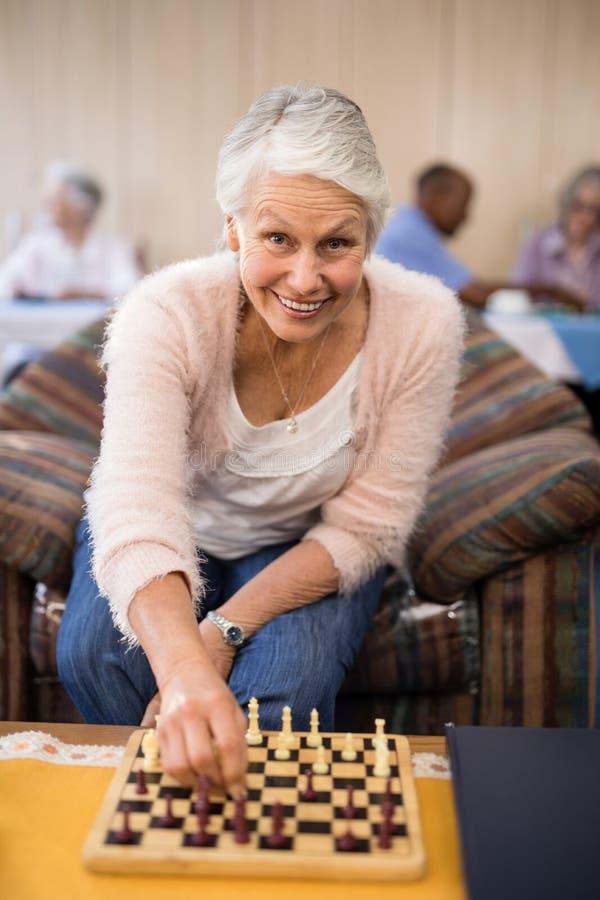 Retrato de la mujer mayor confiada que juega a ajedrez en la tabla fotografía de archivo libre de regalías