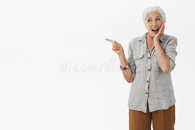 Retrato de la mujer mayor encantadora feliz divertida y emocionada con el pelo blanco en la camisa sport que toca la mejilla suav foto de archivo libre de regalías
