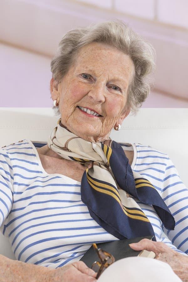 Retrato de la mujer mayor feliz en sala de estar fotos de archivo