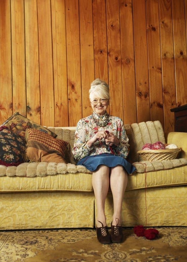 Retrato de la mujer mayor feliz que hace punto en el sofá en casa fotos de archivo libres de regalías