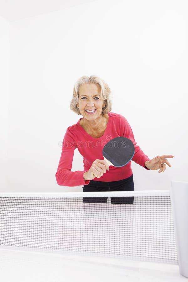Retrato de la mujer mayor feliz que juega a tenis de mesa imágenes de archivo libres de regalías