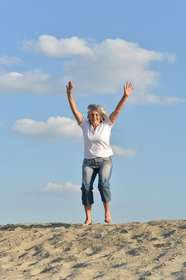 Retrato de la mujer mayor feliz que salta en la colina arenosa foto de archivo libre de regalías