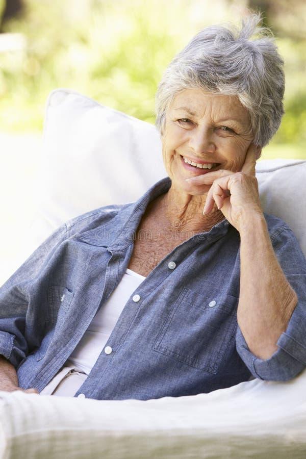 Retrato de la mujer mayor feliz que se sienta en el sofá fotografía de archivo libre de regalías