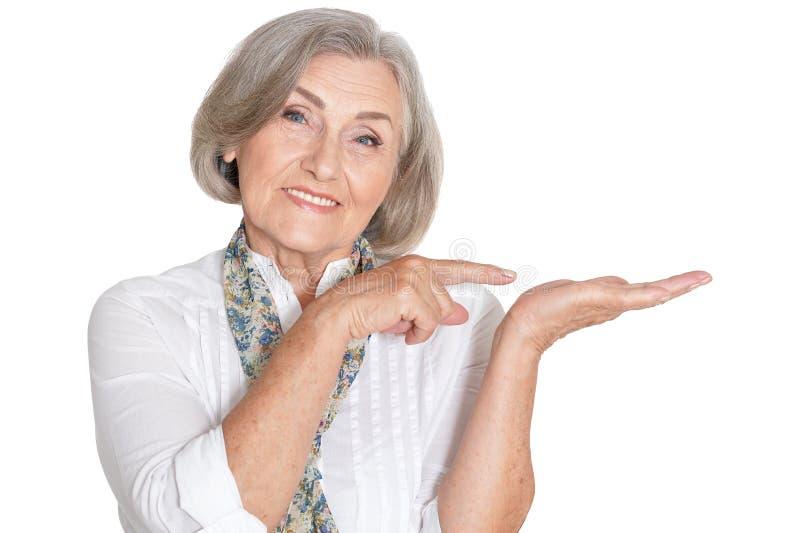 Retrato de la mujer mayor hermosa que señala a la derecha fotografía de archivo libre de regalías