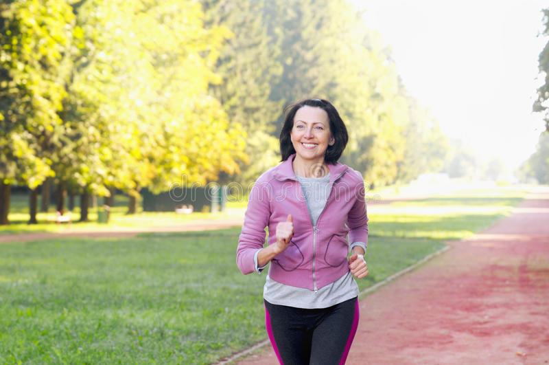 Retrato de la mujer mayor que corre en el parque foto de archivo libre de regalías