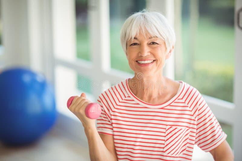 Retrato de la mujer mayor que ejercita con pesa de gimnasia en casa fotos de archivo