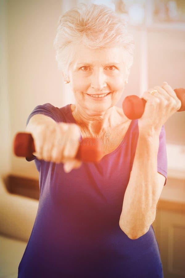 Retrato de la mujer mayor que ejercita con pesas de gimnasia fotografía de archivo