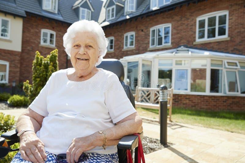 Retrato de la mujer mayor que se sienta fuera de casa de retiro en silla de ruedas motorizada imagenes de archivo