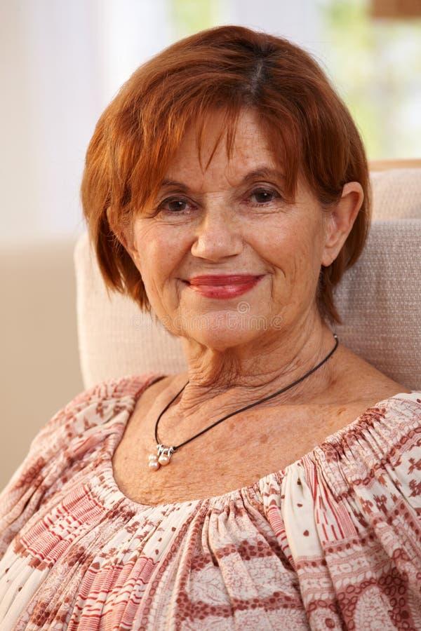 Retrato de la mujer mayor que sonríe en casa imagen de archivo libre de regalías