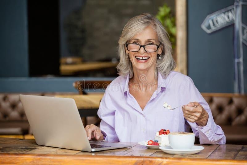 Retrato de la mujer mayor que usa el ordenador portátil mientras que come el desayuno imagen de archivo
