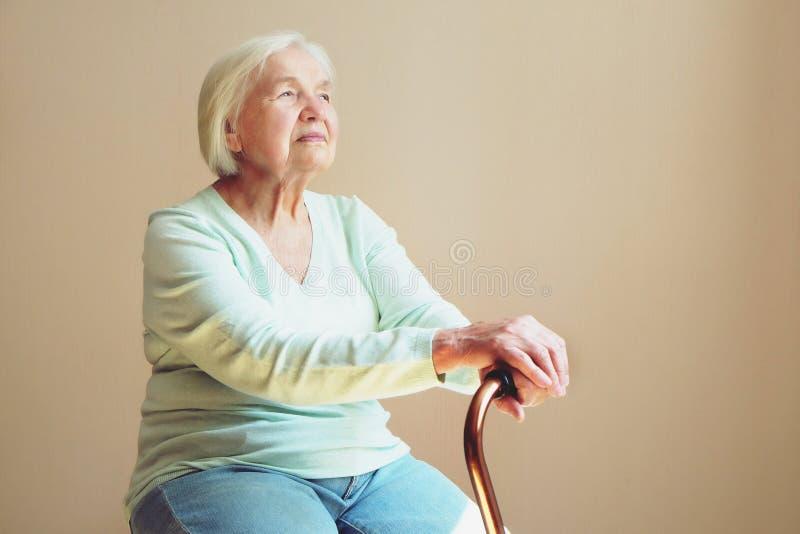 Retrato de la mujer mayor sonriente hermosa con el bastón que camina en fondo ligero en casa imagen de archivo libre de regalías