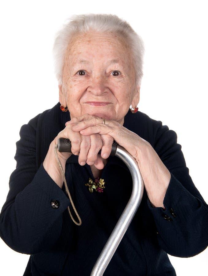 Retrato de la mujer mayor sonriente que se sienta con un bastón imágenes de archivo libres de regalías
