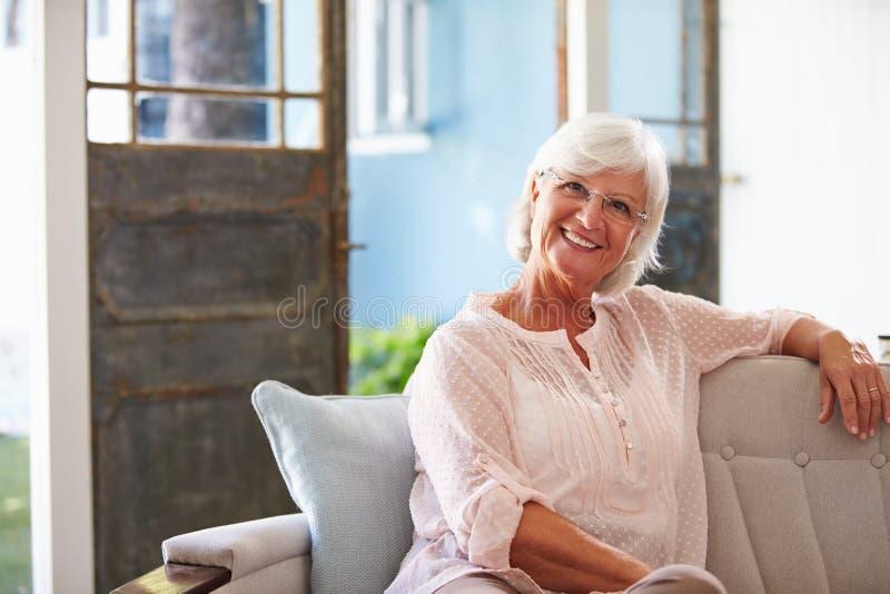 Retrato de la mujer mayor sonriente que se sienta en el sofá en casa imagen de archivo libre de regalías