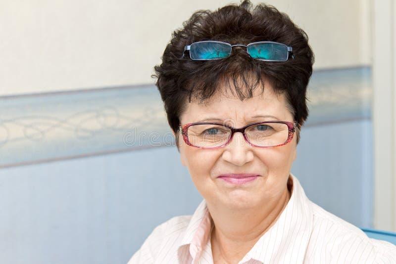 Retrato de la mujer de mediana edad alegre que sostiene dos pares de vidrios imagen de archivo libre de regalías