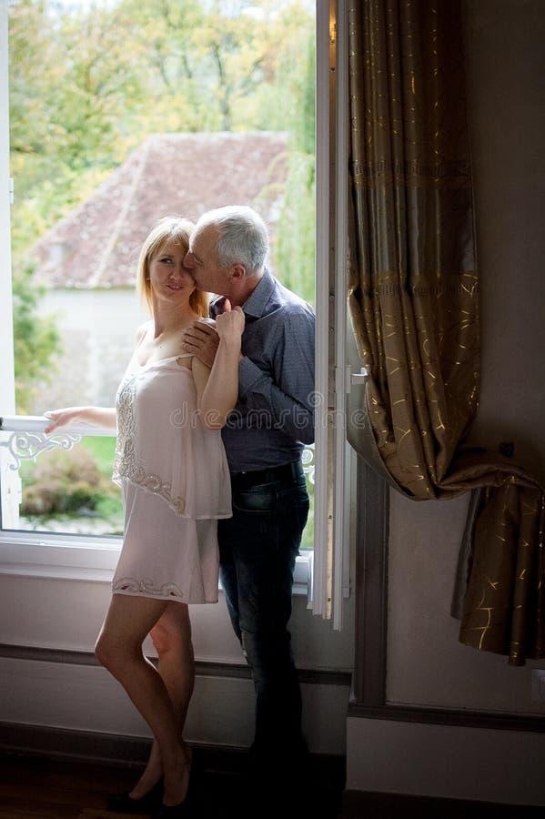 Retrato de la mujer de mediana edad atractiva que disfruta del abrazo de su marido mayor que se coloca cerca de ventana abierta d imágenes de archivo libres de regalías
