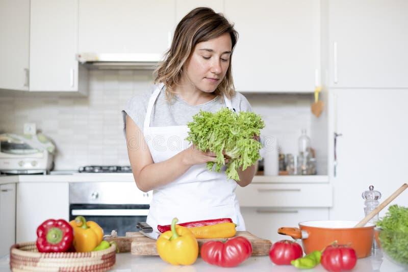 Retrato de la mujer mientras que cocina en la cocina foto de archivo libre de regalías