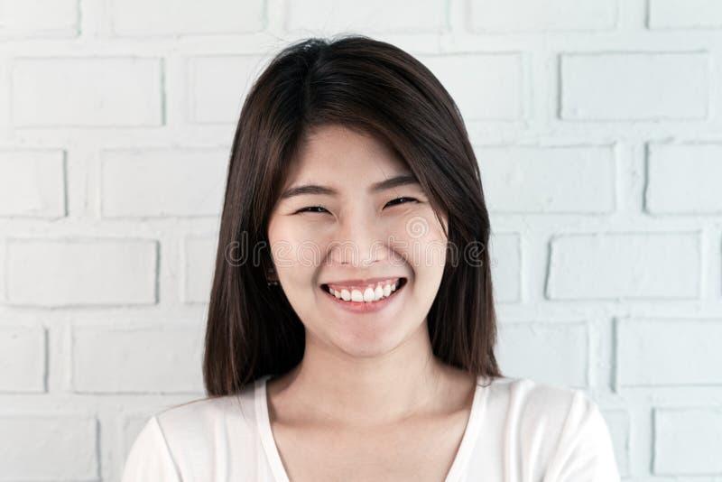 Retrato de la mujer morena asiática atractiva joven que mira la cámara que sonríe con concepto confiado y positivo de la forma de imagen de archivo libre de regalías