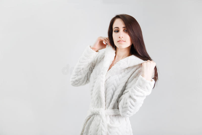 Retrato de la mujer morena hermosa en la albornoz blanca que lleva del fondo blanco foto de archivo