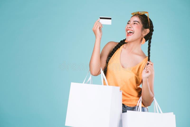 Retrato de la mujer morena joven alegre que sostiene la tarjeta y los panieres de crédito fotografía de archivo libre de regalías