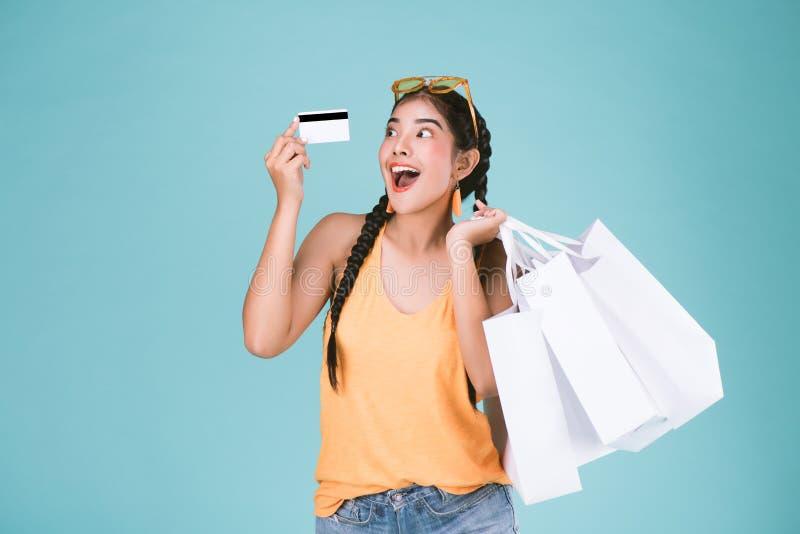 Retrato de la mujer morena joven alegre que sostiene la tarjeta y los panieres de crédito imagenes de archivo