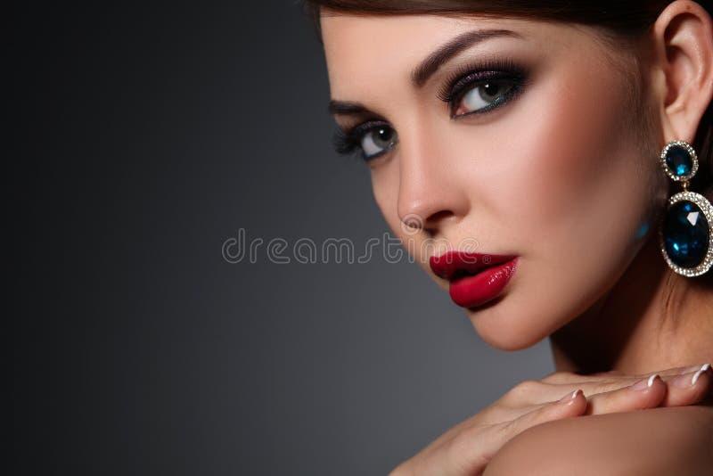 Retrato de la mujer morena joven hermosa en oído fotografía de archivo