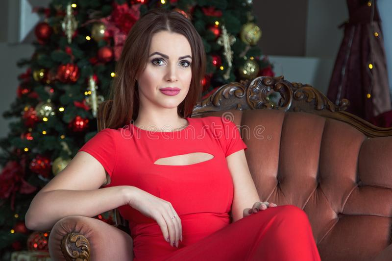 Retrato de la mujer morena joven hermosa que se sienta en un cuarto adornado por Año Nuevo imagen de archivo
