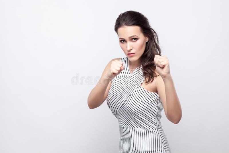 Retrato de la mujer morena joven hermosa seria con maquillaje y la situación rayada del vestido con los puños del boxeo y la mira imagen de archivo