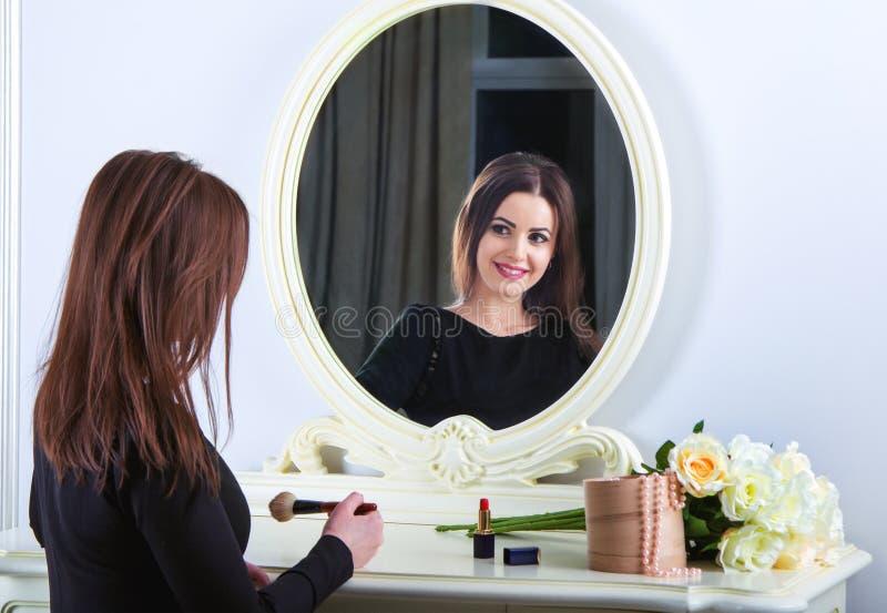 Retrato de la mujer morena sonriente joven hermosa que aplica maquillaje fotografía de archivo