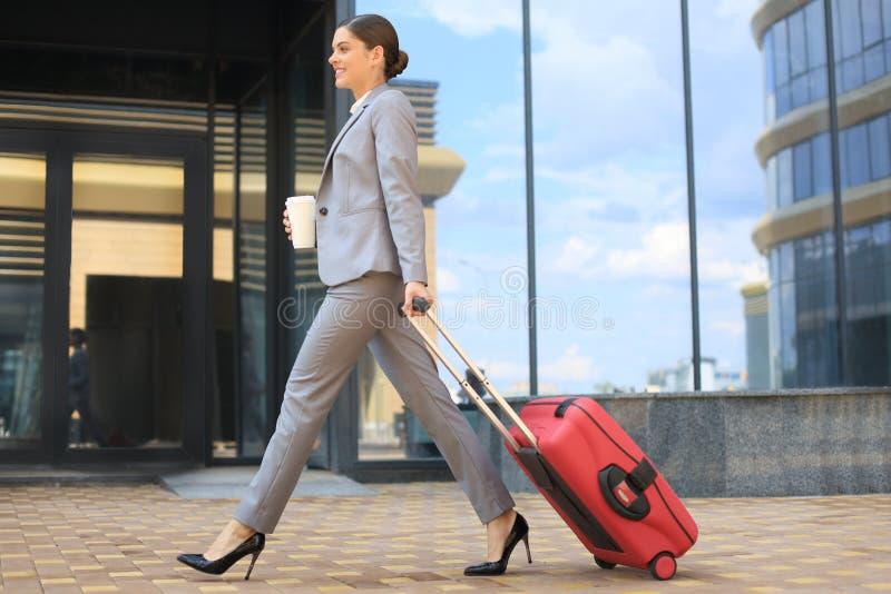 Retrato de la mujer de negocios acertada que entra en el traje que tira del equipaje mientras que camina aire libre foto de archivo libre de regalías