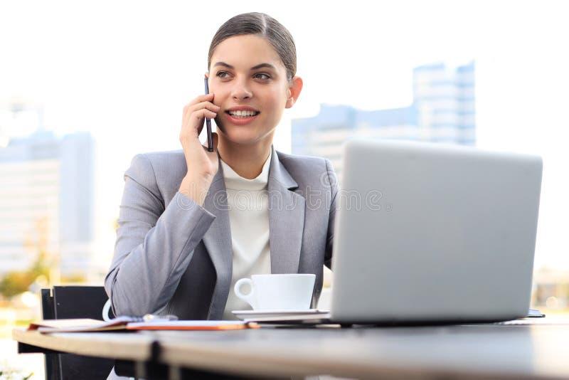 Retrato de la mujer de negocios acertada que habla en el teléfono y que sonríe mientras que trabaja en el café moderno imágenes de archivo libres de regalías