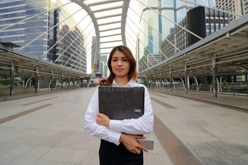 Retrato de la mujer de negocios asiática atractiva joven que coloca y que sostiene la carpeta del documento en el fondo de la ciu fotos de archivo libres de regalías
