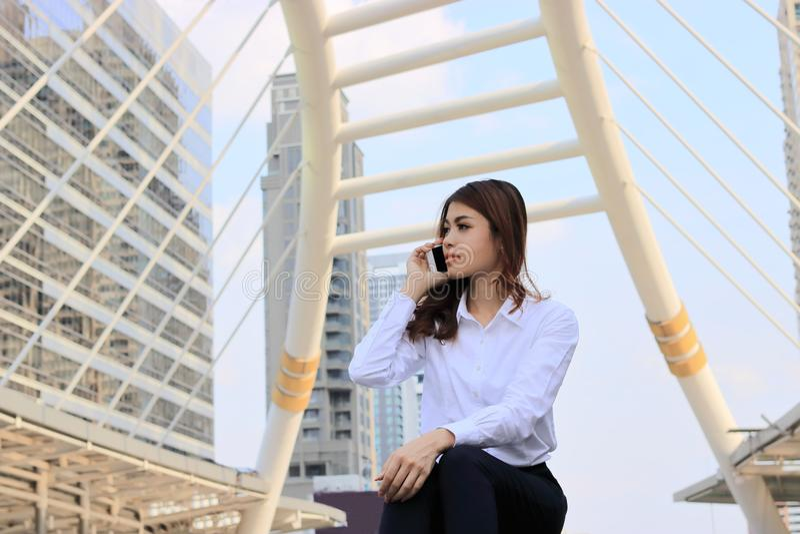 Retrato de la mujer de negocios asiática atractiva joven que habla en el teléfono elegante móvil en el fondo del edificio de la c imagen de archivo libre de regalías